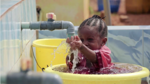 Video image of a child playing in a water bucket in Nigeria.